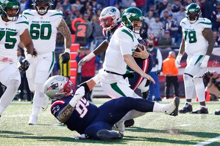 New York Jets quarterback Mike White is taken down by New England Patriots defensive lineman Daniel Ekuale (95) during the first half of an NFL football game, in Foxborough, Mass