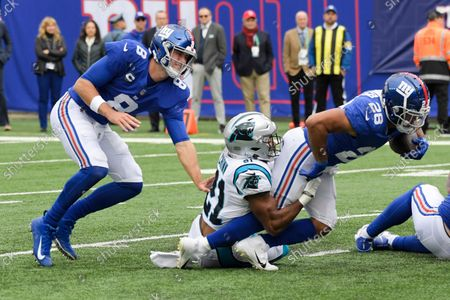 New York Giants quarterback Daniel Jones (8) watches as Carolina Panthers' Jeremy Chinn (21) tackles Devontae Booker (28) during the first half of an NFL football game, in East Rutherford, N.J