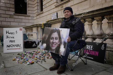 Richard Ratcliffe, husband of detained U.K. charity worker Nazanin Zaghari-Ratcliffe, holds a picture of his wife Nazanin as he sits opposite the Foreign Office in Westminster in London, . The husband of U.K. charity worker Zaghari-Ratcliffe, who has been detained for more than five years in Iran, has gone on a hunger strike again after a court decided she has to spend another year in an Iranian prison