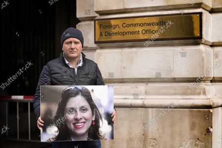 Richard Ratcliffe, husband of detained U.K. charity worker Nazanin Zaghari-Ratcliffe, holds a picture of his wife Nazanin as he stands outside the Foreign Office in Westminster in London, . The husband of U.K. charity worker Zaghari-Ratcliffe, who has been detained for more than five years in Iran, has gone on a hunger strike again after a court decided she has to spend another year in an Iranian prison