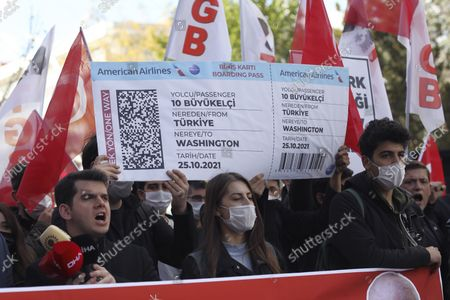 Members of a Turkish group hold a symbolic boarding pass for 10 foreing ambassadors as they stage a protest near the U. S. Embassy to support Turkey's President Recep Tayyip Erdogan, in Ankara, Turkey, . Erdogan last Saturday announced he ordered 10 ambassadors, including those from the US, Germany and France, be declared persona non grata, following a joint statement from the envoys calling for the release of Turkish activist Osman Kavala
