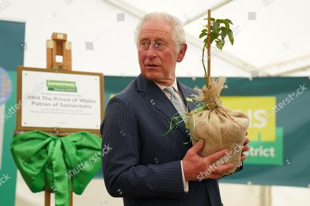 Prince Charles, Patron of Samaritans, with a Samaritans Rose during a visit to the Gloucester and District Branch of Samaritans in Gloucester, to celebrate their 50th Anniversary and hear about the recent work of the charity.