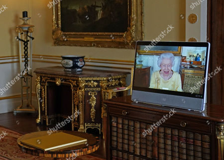 Queen Elizabeth II appears on a screen via videolink from Windsor Castle, where she is in residence, during a virtual audience to receive the Ambassador from the Republic of Korea, Gunn Kim, accompanied by HeeJung Lee (not seen), at Buckingham Palace, London.