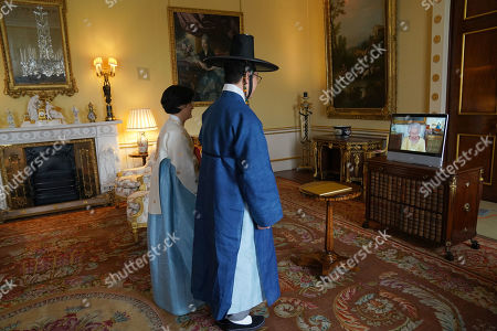 Queen Elizabeth II appears on a screen via videolink from Windsor Castle, where she is in residence, during a virtual audience to receive the Ambassador from the Republic of Korea, Gunn Kim, accompanied by HeeJung Lee (left), at Buckingham Palace, London.