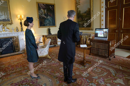 Queen Elizabeth II appears on a screen via videolink from Windsor Castle, where she is in residence, during a virtual audience to receive the as Ambassador from the Swiss Confederation, Markus Leitner, accompanied by his wife Nicole Leitner, at Buckingham Palace, London.