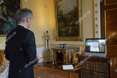 Queen Elizabeth II appears on a screen via videolink from Windsor Castle, where she is in residence, during a virtual audience to receive the as Ambassador from the Swiss Confederation, Markus Leitner at Buckingham Palace, London.