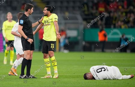 Stock Image of Dortmund's Emre Can, centre, argues with referee Matthias Jollenbeck as Ingolstadt's Fatih Kaya lies on the pitch in pain during the German Soccer Cup match between Borussia Dortmund and FC Ingolstadt 04 in Dortmund, Germany