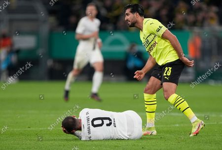 Ingolstadt's Fatih Kaya, left, lies on the pitch in pain after duel with Dortmund's Emre Can, right, during the German Soccer Cup match between Borussia Dortmund and FC Ingolstadt 04 in Dortmund, Germany