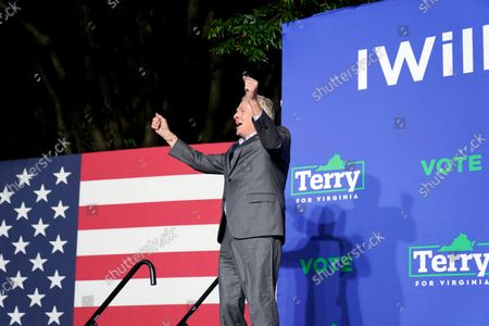 Democratic gubernatorial candidate former Virginia Gov. Terry McAuliffe cheers on stage as he arrives to speak during a rally, in Arlington, Va. McAuliffe will face Republican Glenn Youngkin in the November election