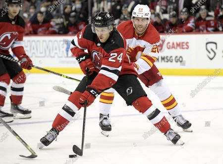 New Jersey Devils defenseman Ty Smith (24) skates with the puck as he is pursued by Calgary Flames center Blake Coleman (20) during the first period of an NHL hockey game, in Newark, N.J