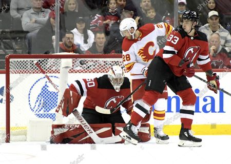 Calgary Flames center Elias Lindholm (28) tips the puck into the net for a goal past New Jersey Devils goaltender Nico Daws (50) as Devils defenseman Ryan Graves (33) looks on during the first period of an NHL hockey game, in Newark, N.J