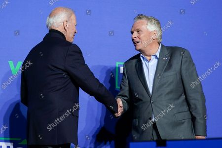 President Joe Biden shakes hands with Democratic gubernatorial candidate, former Virginia Gov. Terry McAuliffe during a rally, in Arlington, Va. McAuliffe will face Republican Glenn Youngkin in the November election