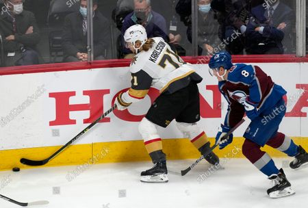 Vegas Golden Knights center William Karlsson, left, reaches out to control the puck as Colorado Avalanche defenseman Cale Makar covers in the first period of an NHL hockey game, in Denver