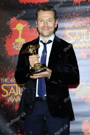 Leigh Whannell poses with his award in the press room for the 46th Annual Saturn Awards held at The Los Angeles Marriott Burbank Airport Hotel Convention Center, Burbank, California, USA, 26 October 2021. The Saturn Awards honors the best in science fiction, fantasy, horror and other genres in film, television, home media releases, and theatre.