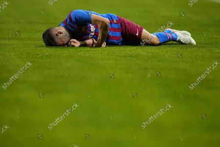 Barcelona's Jordi Alba grimaces in pain after a challenge during a Spanish La Liga soccer match between Rayo Vallecano and FC Barcelona at the Vallecas stadium in Madrid, Spain