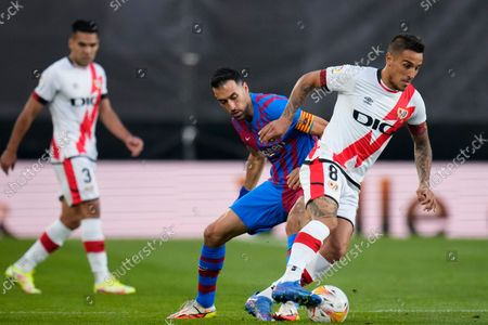 Rayo's Oscar Trejo, right, fights for the ball with Barcelona's Sergio Busquets during a Spanish La Liga soccer match between Rayo Vallecano and FC Barcelona at the Vallecas stadium in Madrid, Spain