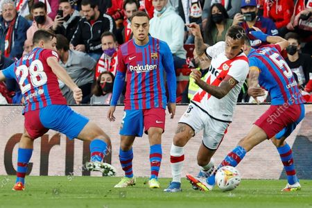 Rayo's Argentinian midfielder Oscar Trejo (2-R) duels for the ball with Barcelona's midfielders Nico Gonzalez (L) and Sergio Busquets (R) and defender Sergino Dest (2-L) during the Spanish LaLiga soccer match between Rayo Vallecano and FC Barcelona at Estadio de Vallecas stadium in Madrid, Spain, 27 October 2021.