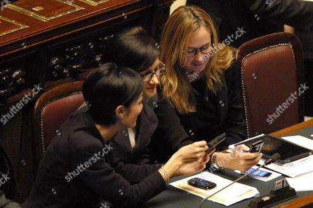Ministers Mara Carfagna, Mariastella Gelmini, Stefania Prestigiacomo watch something funny on a mobile phone