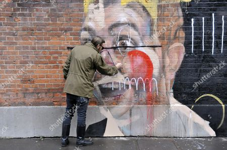 Stock Photo of Charlie Isoe Street Artist Puts The Final Touches To A New Wall Painting On The Offices Of Sir Paul Smith In Covent Garden Today.