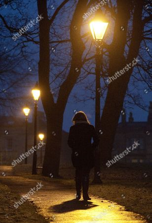 A young woman walking in the Clifton area of Bristol at night
