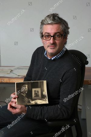 Mark Logue with a photo showing his grandfather Lionel Logue at work