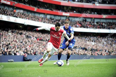 Cesc Fabregas of Arsenal beats Ben Parker of Leeds United to the byline