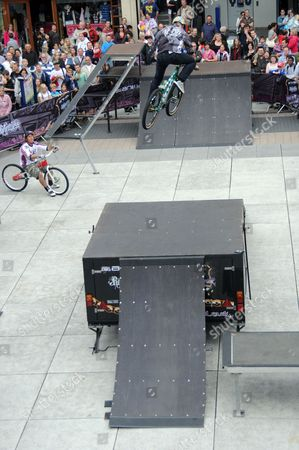 Stock Photo of Freestyle Bike Tour at the Spinaker Shopping Centre, Portsmouth, Britain - Zimbabwean, Blake Samson  in the air and Britian's Martyn Ashton looking on.