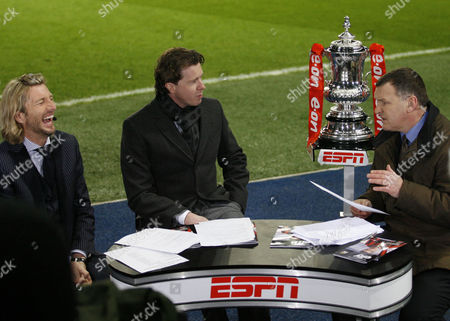 The FA Cup trophy is positioned on an ESPN stand next to presenters Robbie Savage, Steve Mcmanaman and Ray Stubbs
