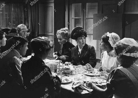 Left to right, around the table, Evin Crowley as Emily, Brian Osborne as Pearce, George Innes as Alfred, Gordon Jackson as Mr Hudson, Patsy Smart as Roberts, Pauline Collins as Sarah, Jean Marsh as Rose and Angela Baddeley as Mrs Bridges
