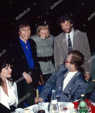 Sir Elton John and his wife Renate Blauel with Bill Wyman, Pattie Boyd and Eric Clapton at the Ivor Novello Awards, London
