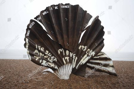Stock Photo of The vandalised sculpture - 'The Scallop' by Maggie Hambling. Aldeburgh beach, Suffolk, England, Britain.