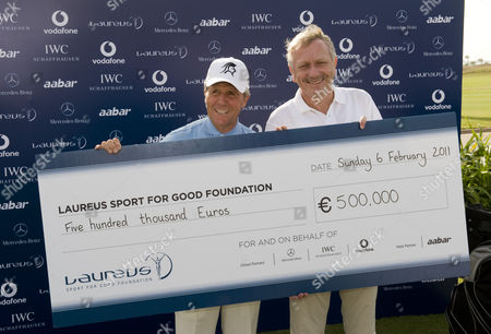 Gary Player and Dr Joachim Schmidt, with a cheque for 500,000 Euros, donated to the Laureus Sport for Good Foundation by the Global Partners