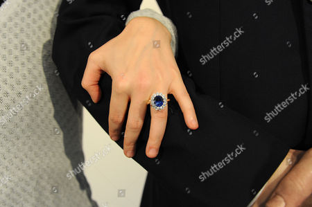 Finger slipped through 'Kate Middleton's engagement ring on the arm of 'Prince William'