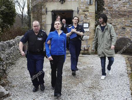Stock Image of The border officers take Olena Petrovich [Carolin Stoltz] away as Eli Dingle [Joe Gilgun] has to be held back by Marlon Dingle