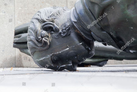 The fallen statue of John Robert Godley - founder of Christchurch in 1850 - lies nose down in the dirt of Cathedral Square