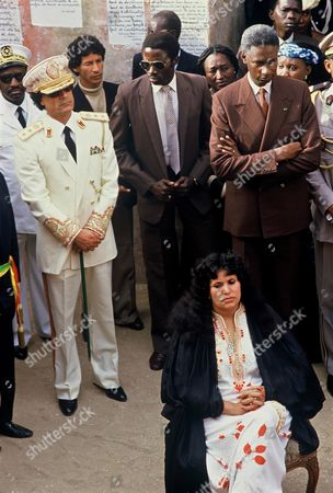 Stock Picture of Colonel Muammar Gaddafi and Senegalese President Abdou Diouf during a ceremony with Moammar Gaddafi's second wife Safia Farkash (sitting in a chair).