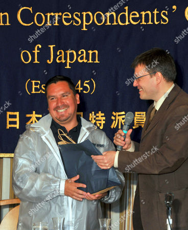 Edison Pena, one of 33 Chilean miners rescued last October, receives a birthday present from Martin Koelling, vice president of Tokyo's Foreign Correspondents Club