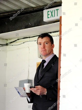 The Port Vale Manager Jim Gannon stands below an exit sign