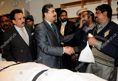 Prime Minister Yousaf Raza Gillani consoles relatives next to the body of Pakistan's federal minister for minority affairs Shahbaz Bhatti after his assassination.