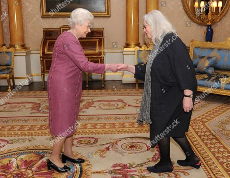 Queen Elizabeth II presents poet Gillian Clarke with her Gold Medal for Poetry at Buckingham Palace