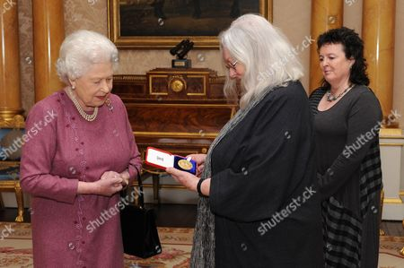 Queen Elizabeth II presenting poet Gillian Clarke (centre) with her Gold Medal for Poetry watched by Poet Laureate Carol Ann Duffy (right)
