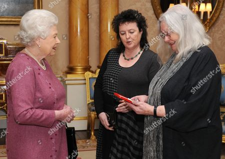 Stock Image of Queen Elizabeth II presenting poet Gillian Clarke (far right) with her Gold Medal for Poetry watched by Poet Laureate Carol Ann Duffy (centre)