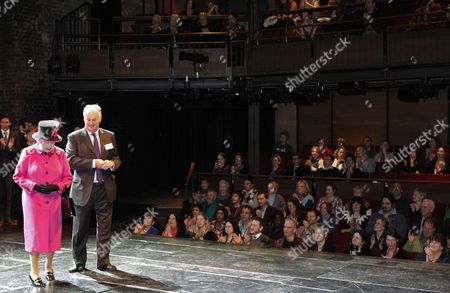 Stock Image of Queen Elizabeth II walks on stage with chairman of the Royal Shakespeare company Christopher Bland