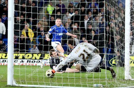 Ipswich Town goalkeeper Marton Fulop makes a save from Cardiff City striker Craig Bellamy
