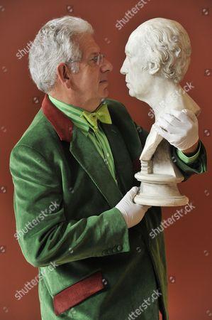 Adam Hart-Davis holds an original bust from the workshop