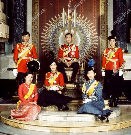 King Bhumibol Adulyadej seated on the throne in Chakri Hall of the Grand Palace, Bangkok, with Queen Sirikit, Crown Prince Maha Vajiralongkorn, Princess Ubolratana Rajakanya, Princess Maha Chakri Sirindhorn, Princess Chulabhorn Walailak, Thailand