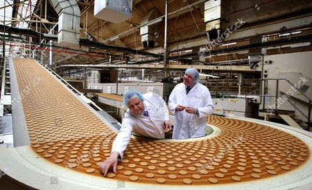Stock Image of Cake Design and Development Head Chef Paul Courtney (R) and Manufacturing Manager Tom Kilcourse perform a quality check on biscuits on the production line
