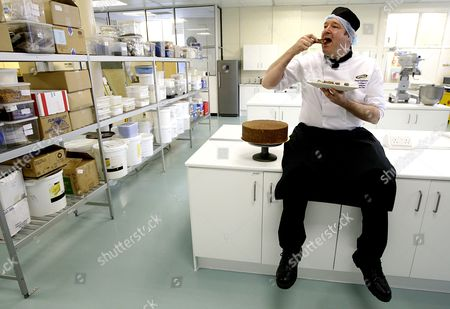 Cake Design and Development Head Chef Paul Courtney tastes a piece of a trial biscuit cake