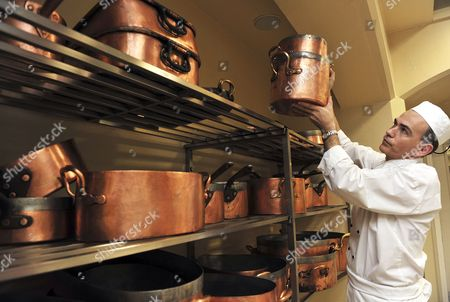 Royal Chef Mark Flanagan, Head of Kitchens at Buckingham Palace, London, lifts copper cooking pots still in use today, with some dating back to King George IV, from a rack in the kitchens