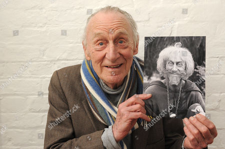 Geoffrey Bayldon holding a photograph of himself as 'Catweazle'